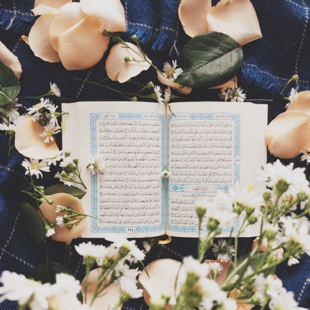 Coran entouré d'un bouquet de fleurs blanches.